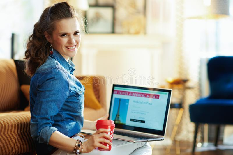 Woman with red coffee cup and online travel site on laptop. Smiling young woman with red coffee cup and opened on laptop online travel & booking agency site in stock photography