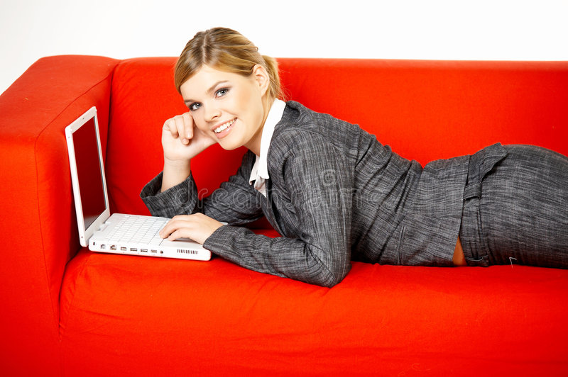 Woman on red couch. Young women is resting on the couch and surfing the internet on her laptop computer royalty free stock images