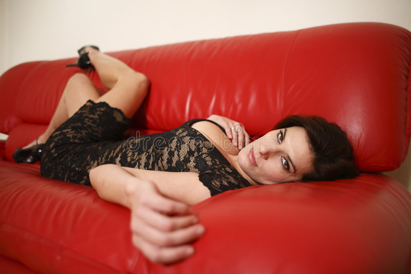 Woman on red couch stock photos