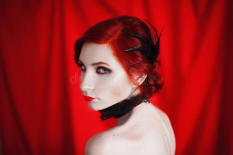 A woman with red curly hair in a black dress and retro makeup on a red background. Red-haired girl with pale skin, blue eyes, a bright unusual appearance, red stock photography