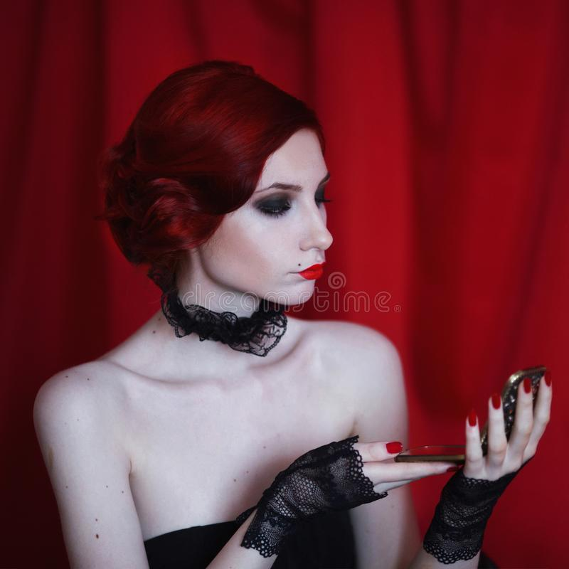 A woman with red curly hair in a black dress and retro makeup on a red background. Woman with red curly hair in a black dress and retro makeup looks in the stock photo