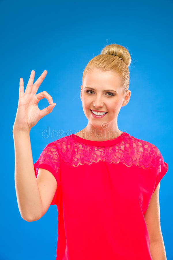 Woman in red doing OK sign. royalty free stock image