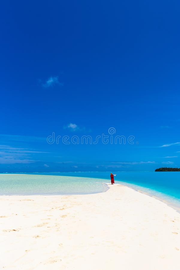 Woman in a red dress on the beach, Aitutaki island, Cook Islands, South Pacific. Copy space for text. Vertical.  royalty free stock photos