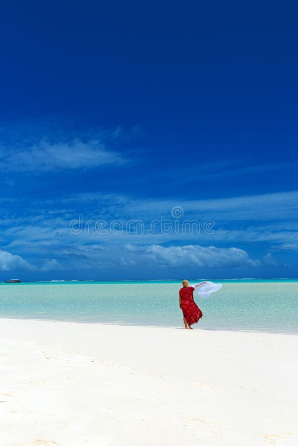 Woman in a red dress on the beach, Aitutaki island, Cook Islands, South Pacific. Copy space for text. Vertical.  royalty free stock photo