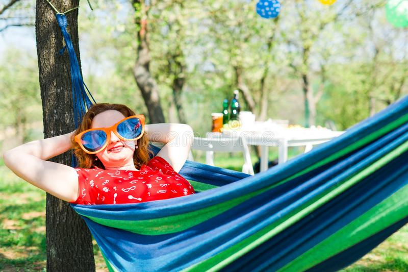 Woman in red dress and big funny sun glasses lying on hammock. Carefree summer garden party stock images