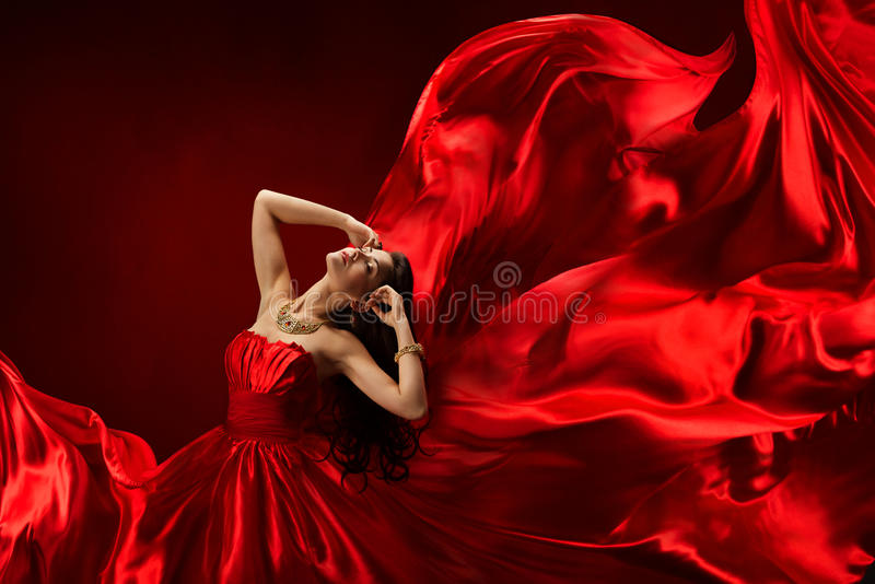 Woman in red dress blowing with flying fabric, fashion posing girl, silk fluttering cloth stock photography