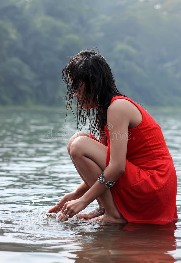 Woman in red dress crouching in lake stock photo