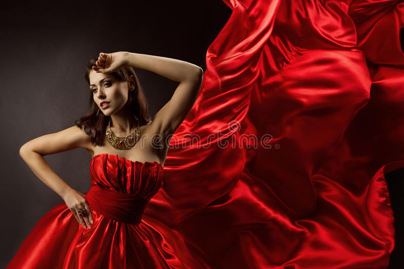 Woman in red dress dancing with flying fabric. On wind flow stock images