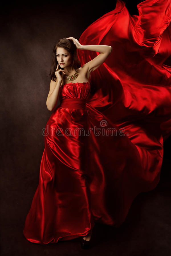 Woman in Red Dress with Flying Fabric, Gown Cloth flowing on wind. Woman in Red Dress with Flying Fabric, Gown Cloth flowing fluttering on wind, Serious Girl stock photography