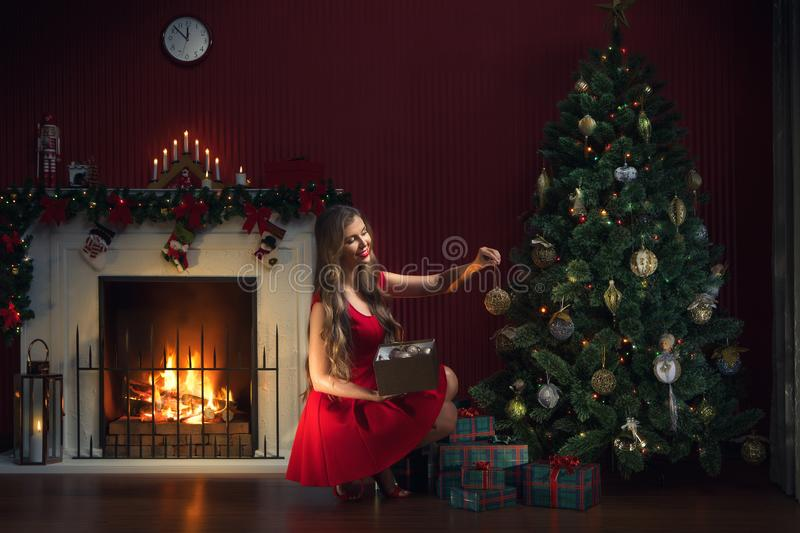 Woman in red dress decorating christmas tree stock photography