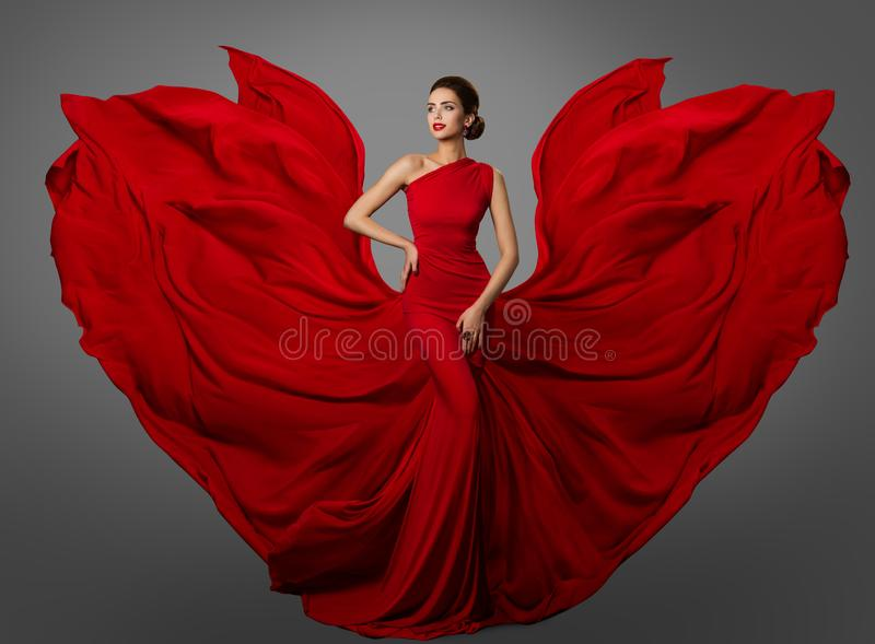 Woman Red Dress, Fashion Model in Long Silk Waving Gown Wings, Flying Fluttering Fabric. Over studio gray background stock photos