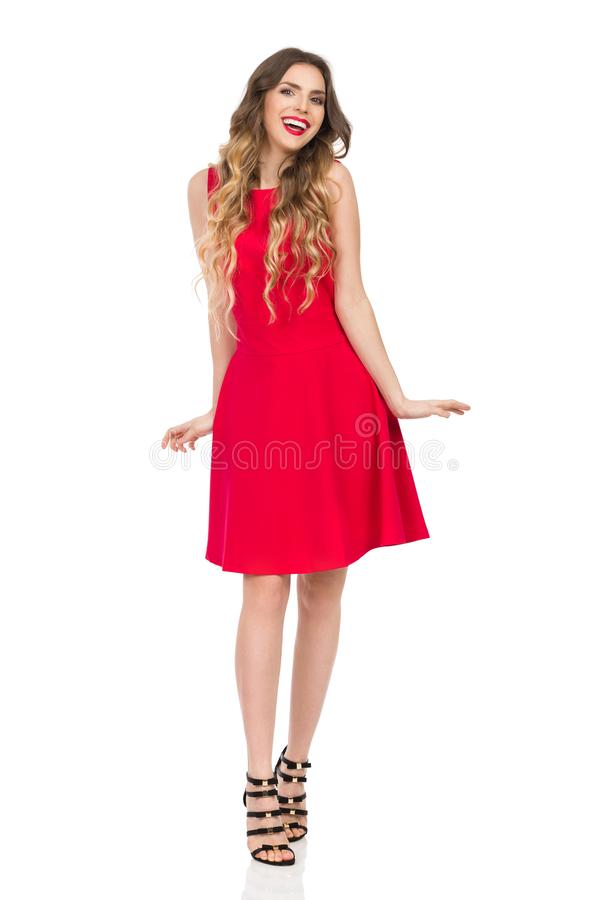 Woman In Red Dress And High Heels Is Smiling And Sneaking Towards Camera. Beautiful young woman in red mini dress and high heels is sneaking towards camera and royalty free stock images
