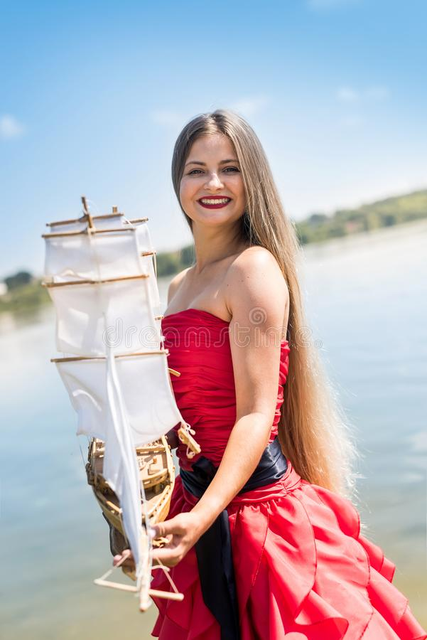 Woman in red dress holding boat model on the beach.  royalty free stock photography