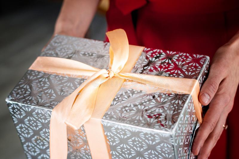 Woman is holding a box gift wrapped in silver wrapping paper and tied up with a pink ribbon royalty free stock photos