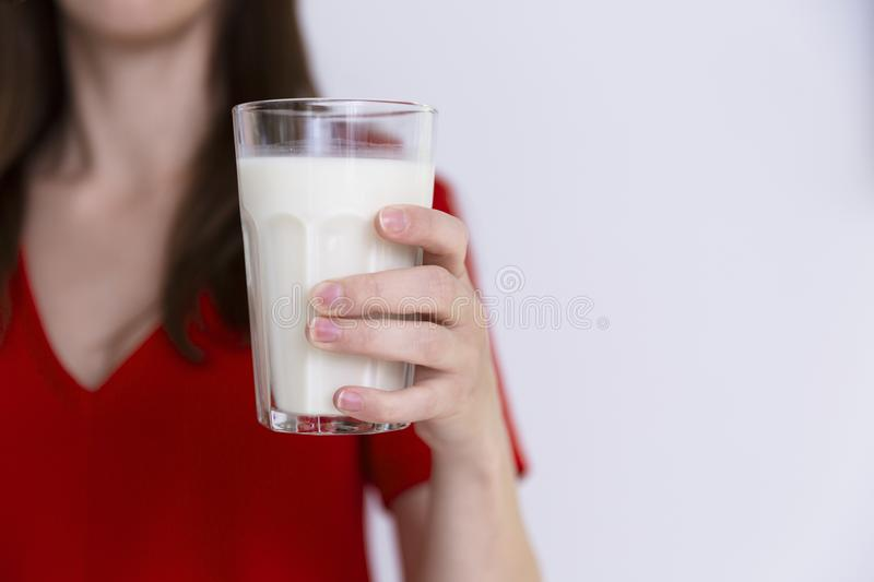 Woman in red dress holding glass of milk. Lactose intolerance, c stock images