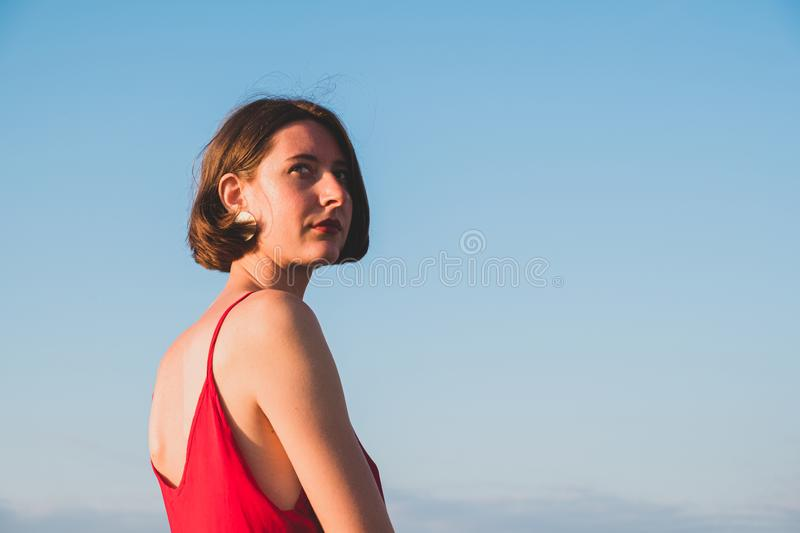 Woman in red dress looking back behind the shoulder stock images