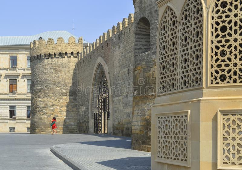 Woman in red dress near old Baku wall with gates stock photo