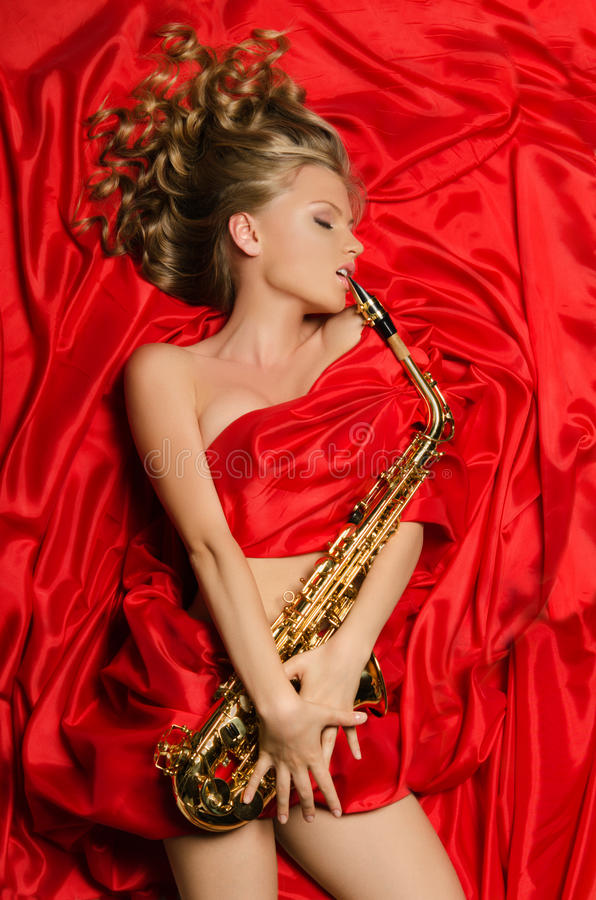 Woman in red dress playing the saxophone royalty free stock photography