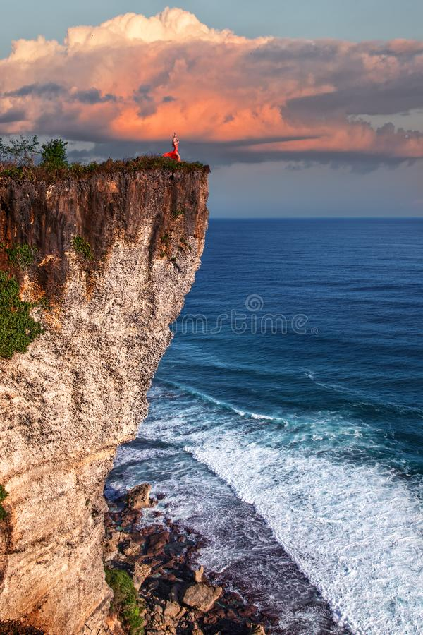 Woman in the red dress posing on the cliff above the ocean stock photography