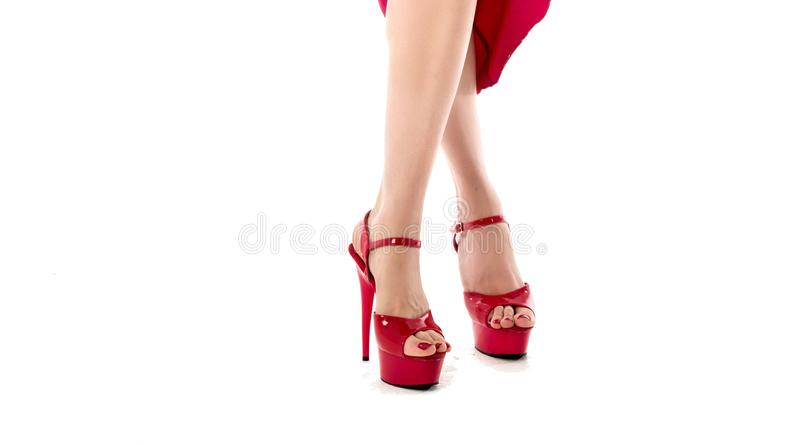 Woman in red dress with legs isolated on white background. On her leg red garter. Garter on her leg ang high-heeled. Shoes royalty free stock photography