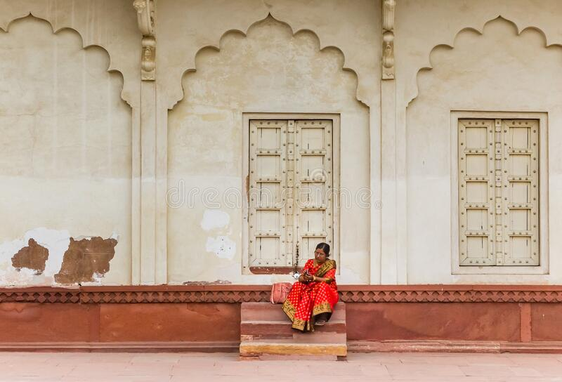 Woman in red dress sitting at the Red Fort in Agra royalty free stock photography