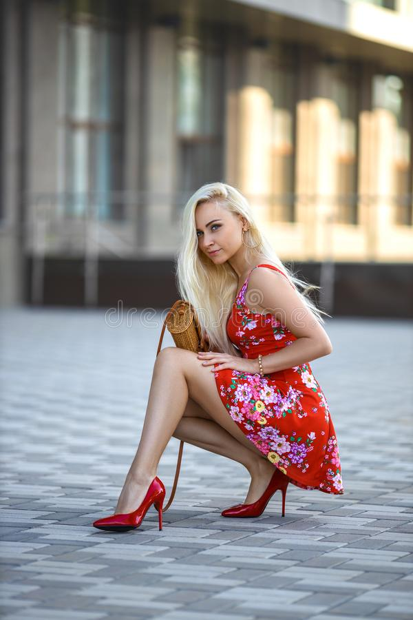 Woman in red dress sitting on the square stock images