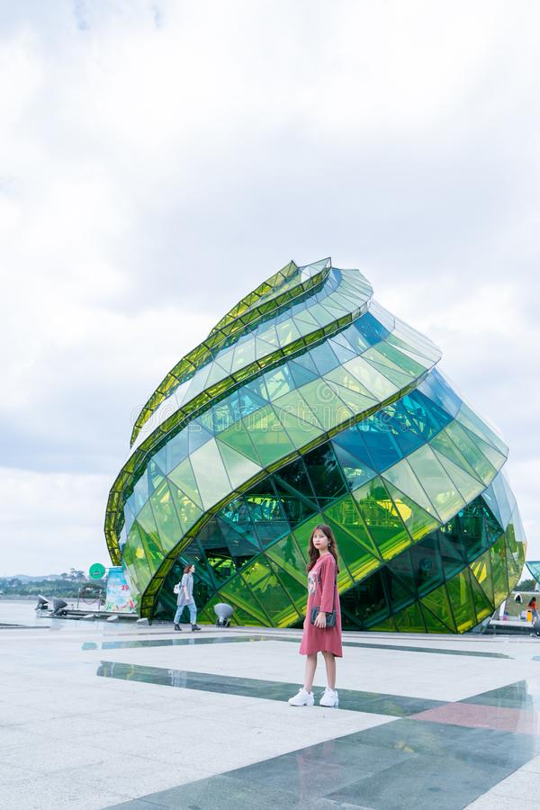 Woman in Red Dress Standing in Front of Green Glass Elliptical Building stock photos