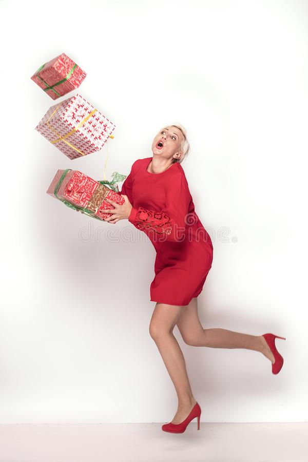 Woman in red dress trying to hold stack of gift boxes, on red studio background. Christmas shopping, copy space royalty free stock image