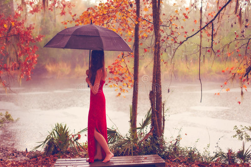 Woman in red dress with umbrella stock images