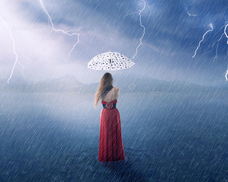 Woman in red dress under umbrella. Beautiful young woman in red dress under umbrella on countryside flooded field on rainy day with thunderstorm cloudy sky stock photos