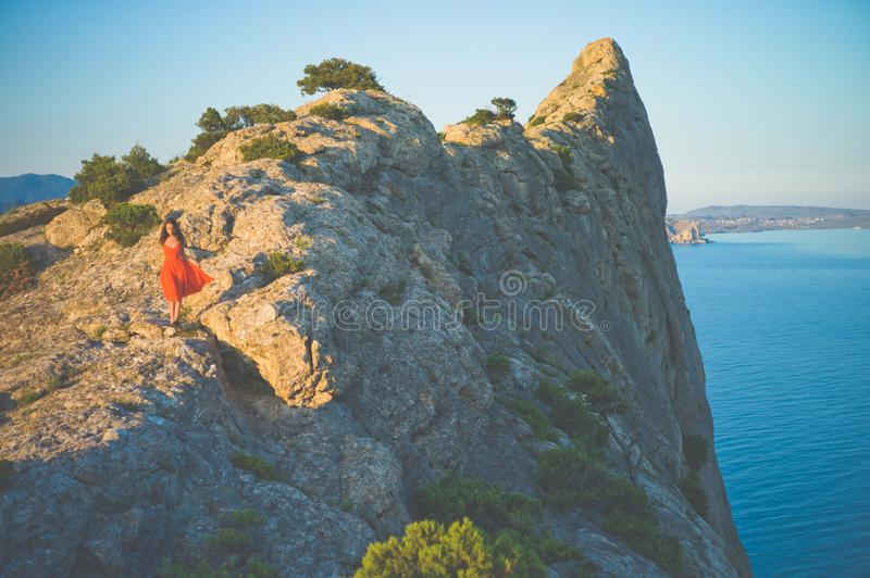 Woman in red dress walking on rock. Outdoor lifestyle photo of woman in red dress walking on rock. Travel background. Tourism royalty free stock photo