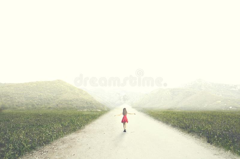 Woman with red dress walks to infinity in the middle of nature royalty free stock photo