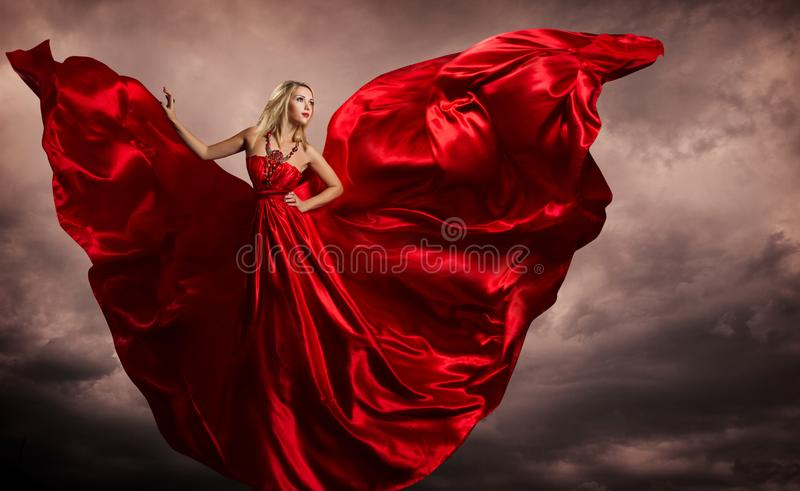 Woman Red Dress Wings, Fashion Model Silk Waving Gown, Flying Fluttering Fabric on Storm Wind. Over evening sky background stock images