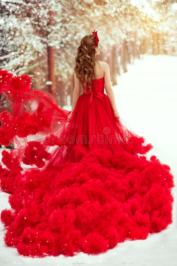 Woman Red Dress and Winter Snow, Fashion Model in Ruched Fluffy Waving Gown, Rear View royalty free stock image