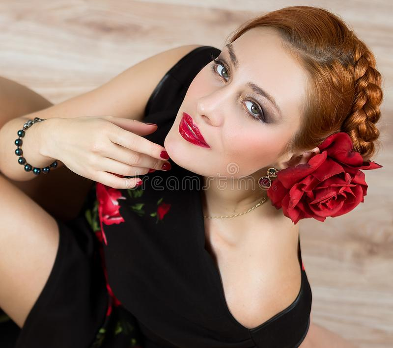 Woman with red flower in black dress portrait stock photo