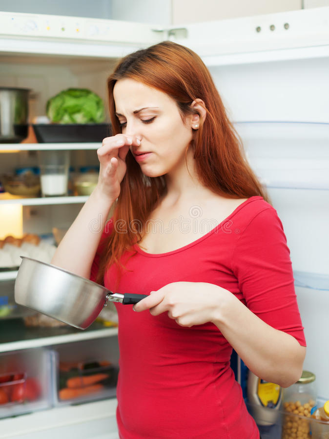 Woman in red with foul food. Near refrigerator stock photo