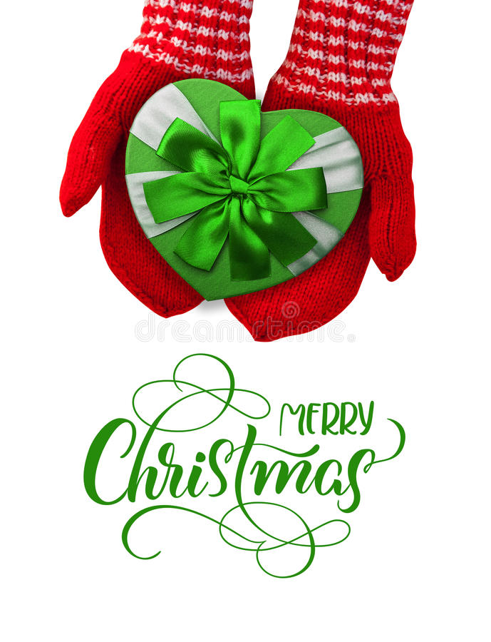 Woman with red gloves holding gift in the shape of a heart and text Merry Christmas. Calligraphy lettering stock photo
