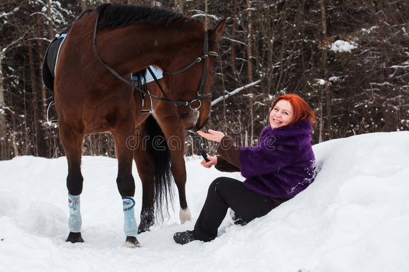 Woman with red hair and big horse outdoor in winter stock photos