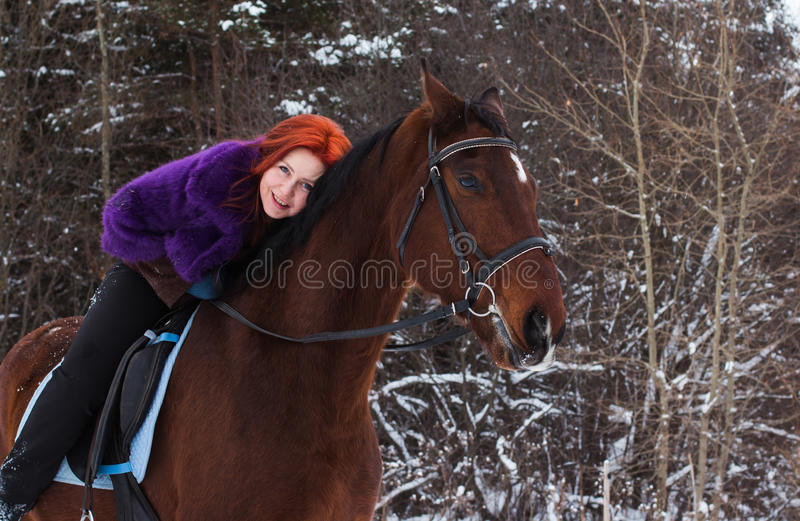 Woman with red hair and big horse outdoor in winter stock photo