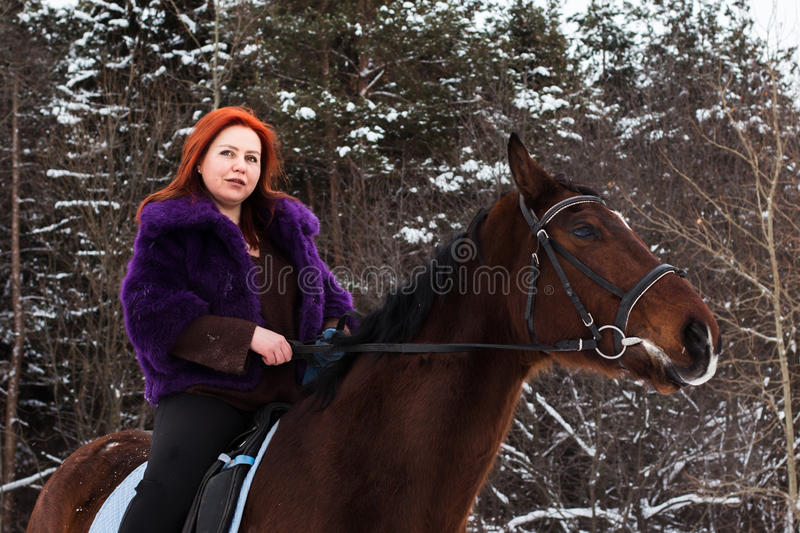 Woman with red hair and big horse outdoor in winter royalty free stock image