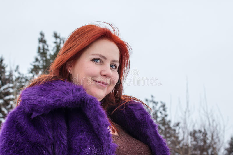 Woman with red hair and big horse outdoor in winter royalty free stock photo
