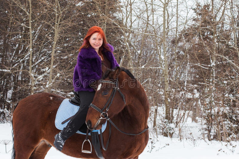 Woman with red hair and big horse outdoor in winter stock photography