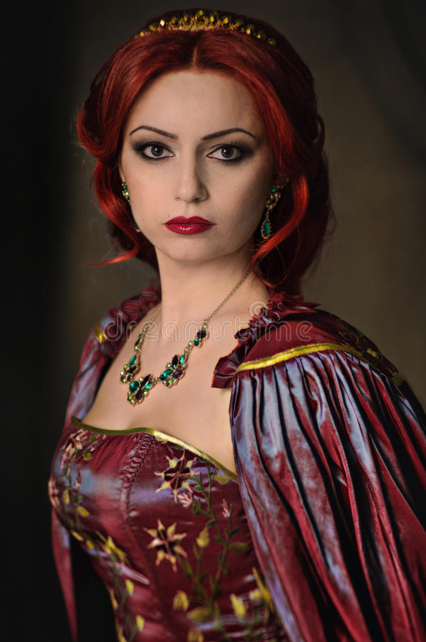 Woman with red hair in elegant royal garb. Woman with red hair wearing elegant royal garb and golden crown stock photo