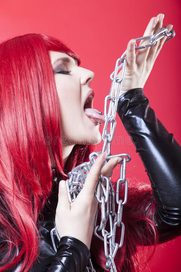 Woman with red hair. Female fetishist licks a steel chain with her long tongue stock images