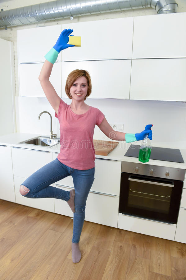 Woman with red hair in rubber washing gloves holding cleaning spray bottle and scourer. Young attractive and happy woman with red hair in rubber washing gloves stock photos