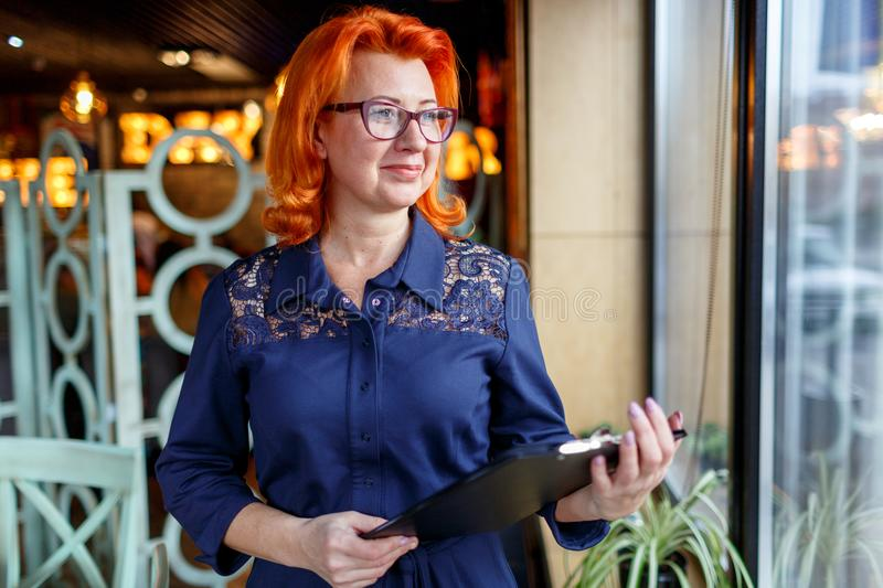 A woman with red hair, stands near the window and looks into the distance, holding a clipboard. stock image