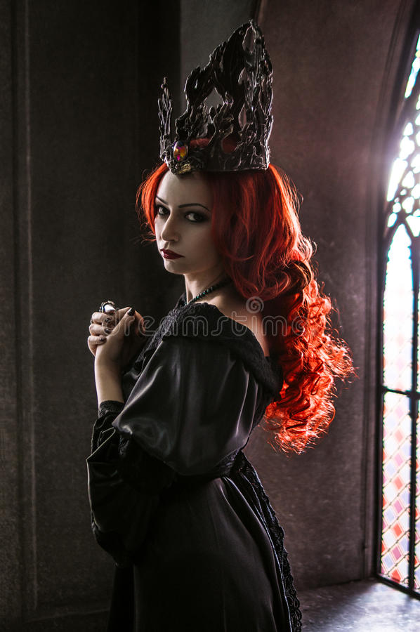 Woman with red hair. Wearing elegant royal garb and crown in ancient castle royalty free stock photos