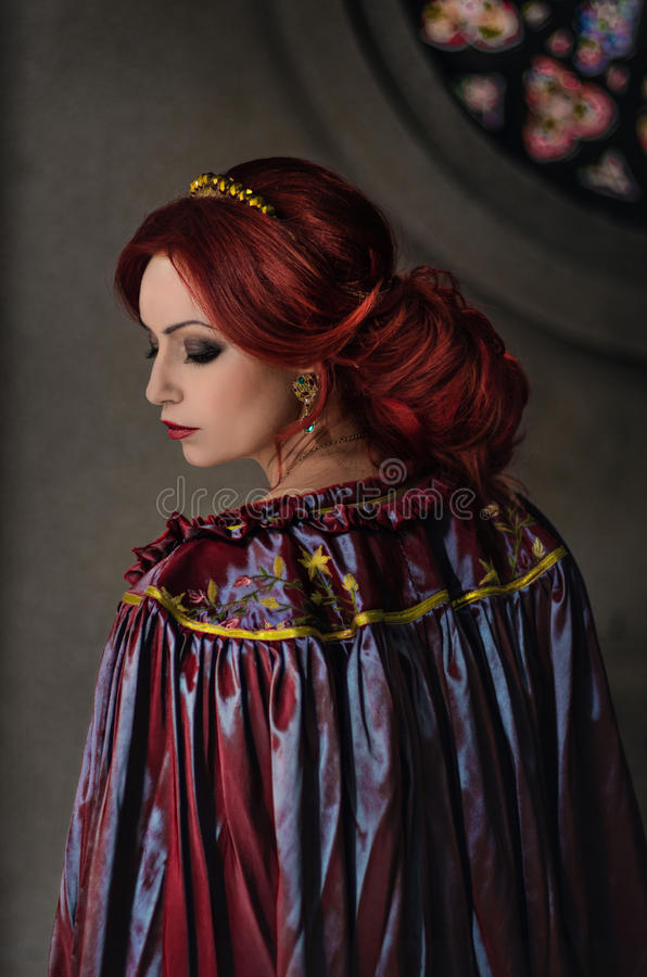 Woman with red hair. Wearing elegant royal garb and golden crown royalty free stock photos