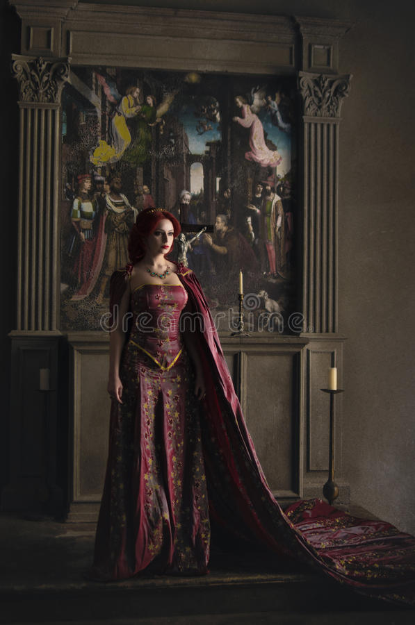 Woman with red hair wearing elegant royal garb. And golden crown in ancient castle stock image