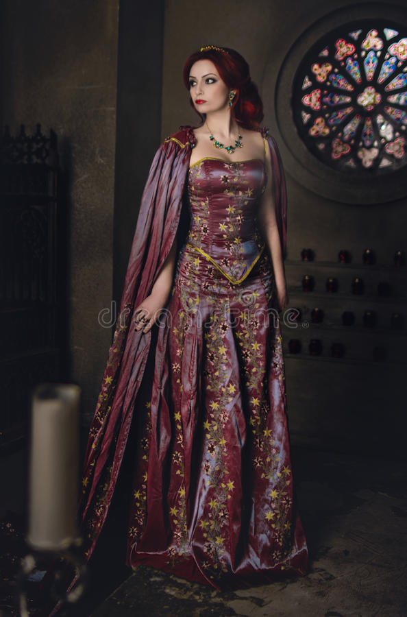 Woman with red hair wearing elegant royal garb. And golden crown in ancient castle royalty free stock photo